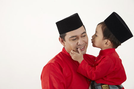 malay boy about to kiss his father