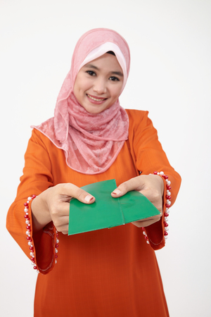 Asian Muslim Malay woman with tudung holding green packet