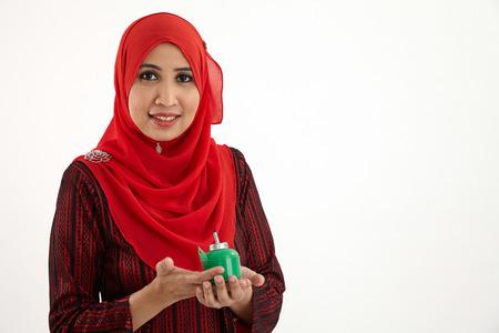malay woman wearing red baju kurung holding a pelita Stok Fotoğraf