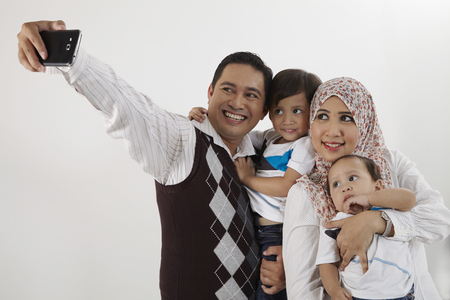 family of four looking taking selfie