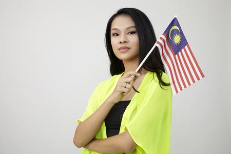 Mujer China sosteniendo una bandera de Malasia sobre el fondo blanco.