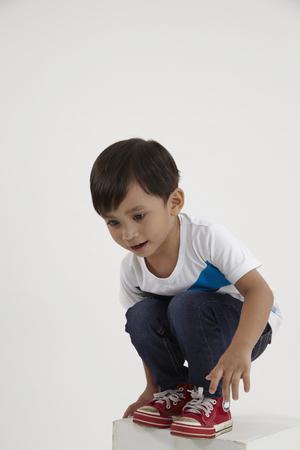 Maleisische jongen hurkt op de doos die op het punt staat te springen