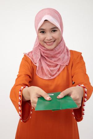 Asiatische muslimische malaiische Frau mit Tudung mit grünem Paket