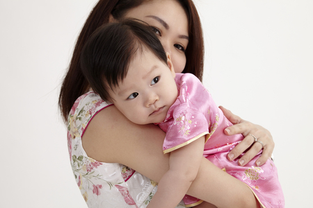 chinese mother hugging her daughter baby