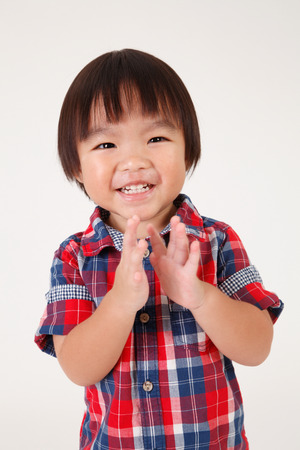 portrait of boy with checker shirt clapping hands