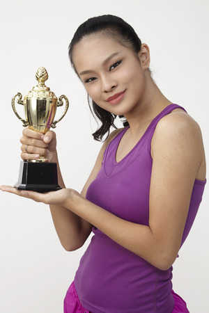 chinese woman holding a golden trophy Stockfoto