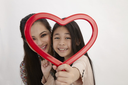 malay mother and daughter holding a red heart shape picture frame facing camera Stock Photo