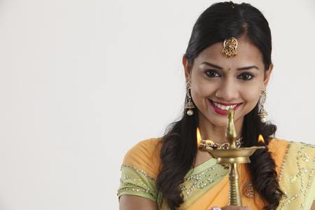Beautiful young Indian woman in traditional sari dress holding a diwali oil lamp light, isolated on white background.