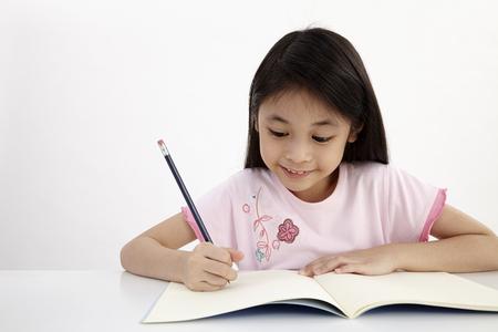 bambina che scrive facendo i compiti Archivio Fotografico