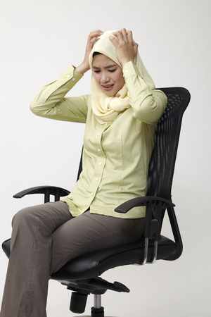 business woman sitting on the office chair feeling sad