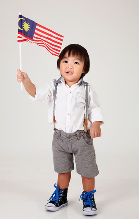 niño chino sosteniendo la bandera de malasia Foto de archivo