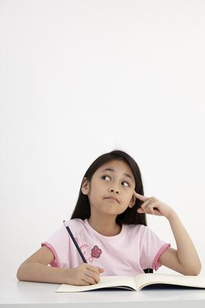 little girl writting doing homework Standard-Bild