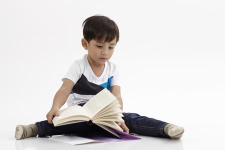 Malay boy sitting reading book Standard-Bild