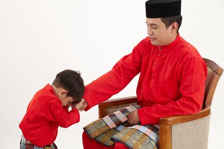 Son greeting or salam to his father during hari raya Stok Fotoğraf