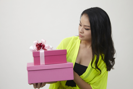 portrait of beautiful girl holding a gift box isolated on white background