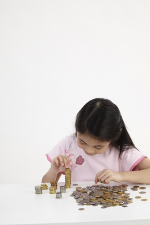 Little girl counts his coins on a table