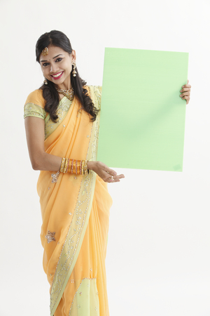 pretty indian woman holding green placard