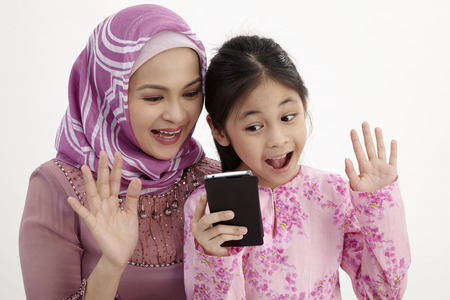 Closeup of excited girl and mother making video call with smart phone
