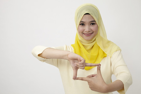 malay woman imitating frame for photo in focus Imagens