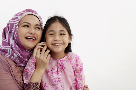 Closeup of excited girl and mother listening to cell phone