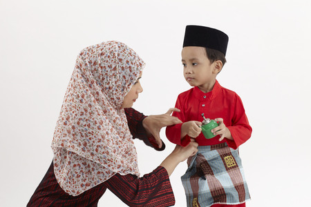 malay woman sdjusting her son baju raya
