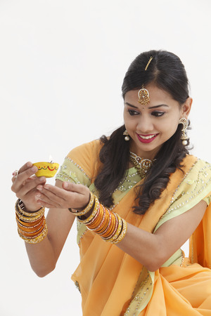 Indian woman in glamorous traditional clothing holding oil lamp