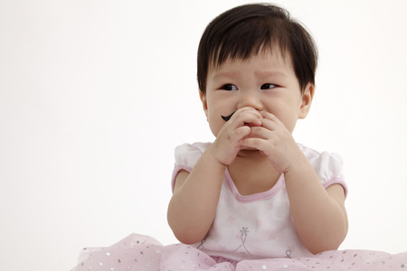 chinese baby girl look funny with paper moustache Foto de archivo