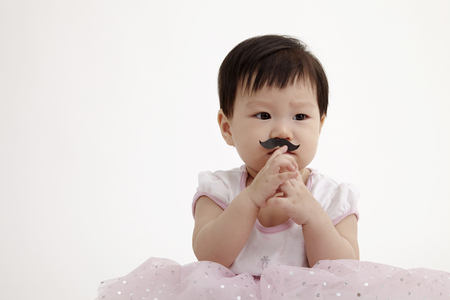 chinese baby girl look funny with paper moustache Imagens