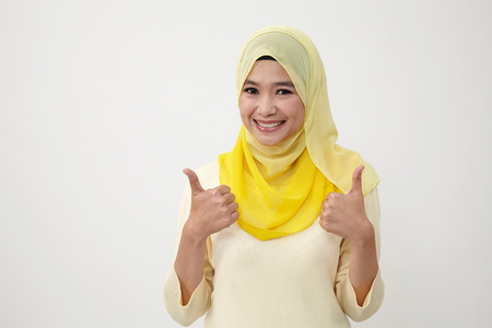 Malay woman with scarf showing thumbs up