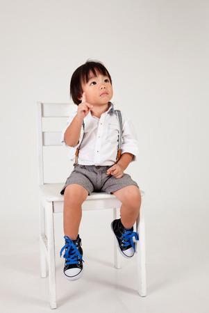 chinesischer Junge sitzt auf dem großen Hocker