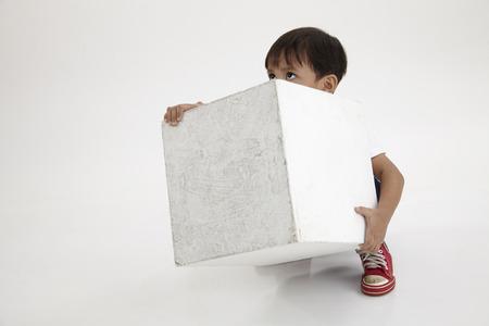 boy try lift a heavy white box