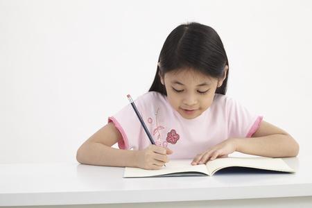 little girl writting doing homework Foto de archivo
