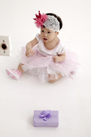 chinese baby wearing party dress with purple gift box