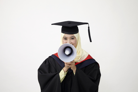 Graduation student shouting through megaphone 免版税图像