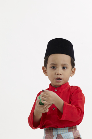 malay boy in red holding an oil lamp