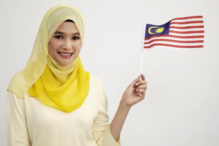malay woman holding a small malaysia flag