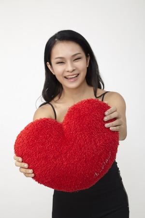 Donna asiatica che tiene un cuscino a forma di cuore rosso.