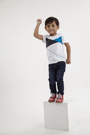 little champion standing on top of box raising his arm