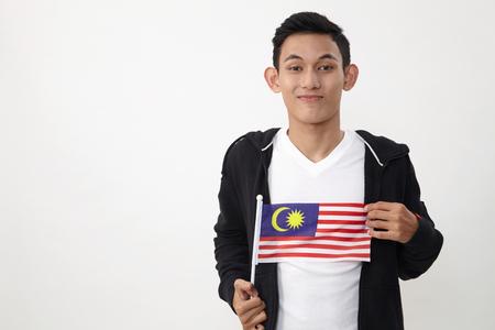 malay teenage holding a small malaysiasia flag