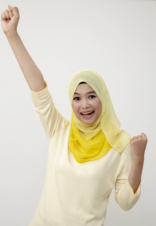 Studio shot of young woman celebrating with arm raised Stock Photography