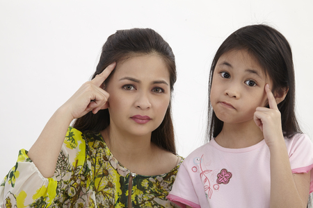 mother and daughter with same expression thinking Stock Photo