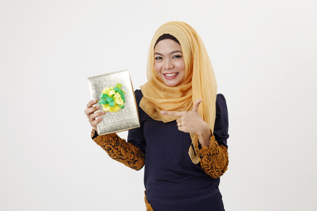 Close up malay woman with tudung holding a raya present