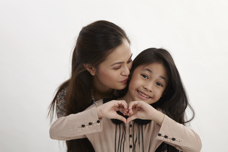 Portrait of happy mother and young daughter with heart shape sign - isolated on white background