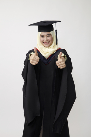 Happy young women in mortarboard  isolated on white
