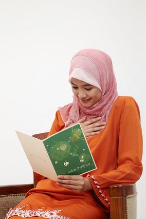 Asian Muslim Malay woman with tudung holding raya greeting card