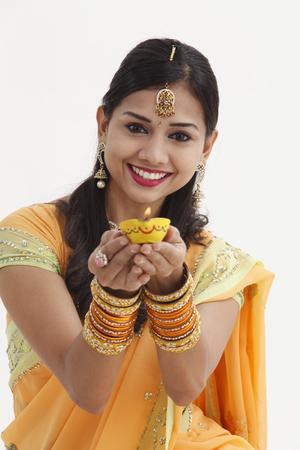 Femme indienne en vêtements traditionnels glamour tenant une lampe à huile Banque d'images