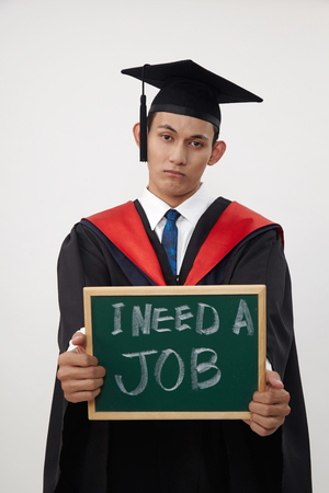 malay graduated student holding a blackboard written need a job Standard-Bild