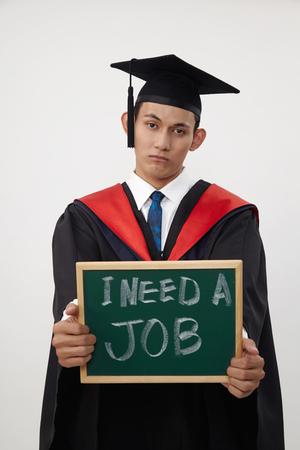malay graduated student holding a blackboard written need a job Standard-Bild