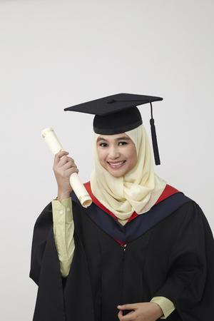 Szczęśliwe młode kobiety w tablicy do zaprawy murarskiej, trzymając dyplom i uśmiechając się do kamery, gdy są odizolowane na białym tle Zdjęcie Seryjne