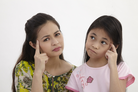 mother and daughter with same expression thinking 版權商用圖片